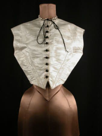 Chemisette, front, circa 1850, white moire, waistcoat shaped and boned laced at back. Black silk buttons, neck trimmed with lace threaded with black velvet ribbon, National Trust Collections.: