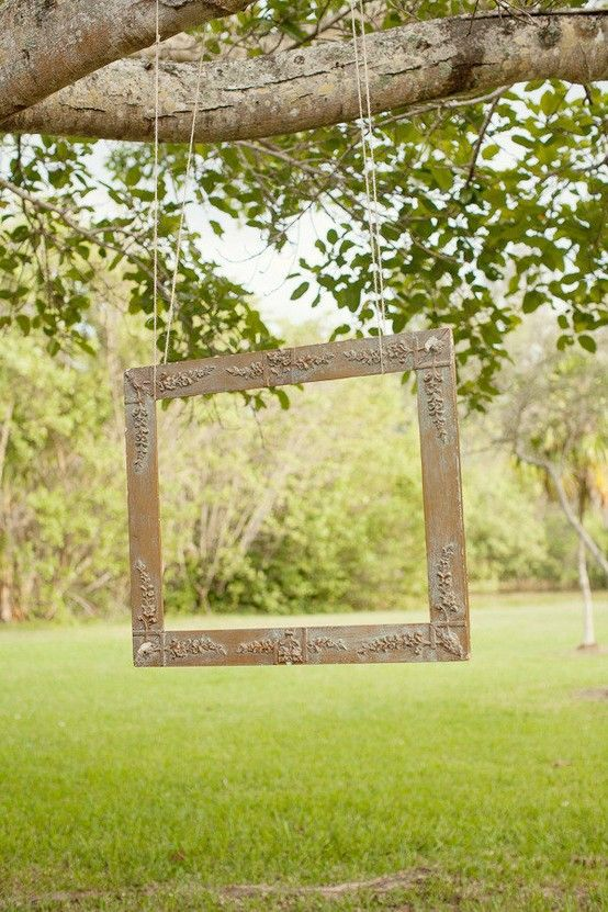 Wedding Photos - Instead of a photo booth, hang an empty picture frame from a tree branch at a rustic wedding reception.: