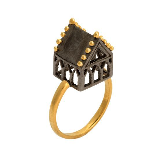 Part of the Hoyz ring collection, this exquisite piece features the Sanctuary design in oxidized silver with gold plate. The ring is a beautiful statement piece of jewellery, designed to be worn. Combining historical origins with contemporary style, these updated designs strike a perfect balance of new yet old. Inspired by antique Jewish wedding rings, the architectural symbol traditionally represented the marital home of the new couple. The detailed house or 'hoyz' in yiddish was a ...:
