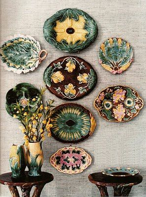 , perhaps - and corn-shaped pitchers, possibly American. Center row from top down: A corn platter, pear clusters adorning a brown dessert platter, a bread plate is marked by a starburst of wheat, a plate decorated with grapes. Right row from top down: A banana-leaf fruit plate, a berry plate, a strawberry plate adorned with leaves and flowers.