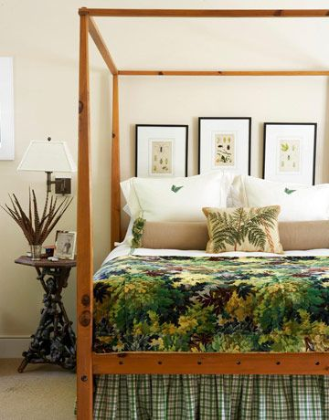 Embroidered shams, a needlepoint throw pillow, and a tapestry coverlet echo the woodland scenery outside this master bedroom's window.
