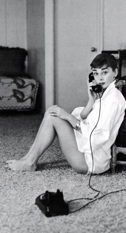 Audrey Hepburn taking a call.: