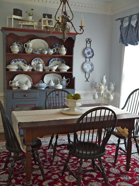 Kitchen table with runner, blue and white dishes displayed, crown molding and a red touch in the rug.